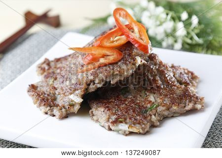 Grilled meat on white plate with sliced chili
