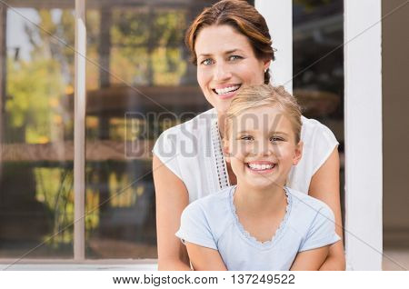 Mother and smiling daughter sitting outside the house. Happy mom and little girl enjoying in a summe