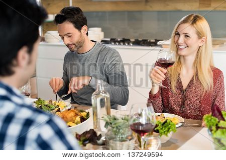 Happy young woman drinking a glass of red wine while talking to friend. Friends having lunch or dinner at home. Happy reunion of long lost friends.