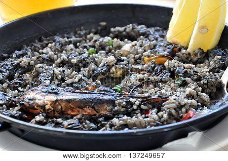 Plate of black paella with sea food