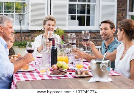 Happy family raising their glasses during lunch. Generation family toasting with red wine at picnic table. Parents with grandparents and children celebrating with party.