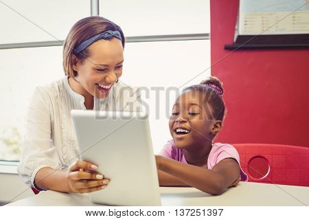 Teacher and school girl using digital tablet in classroom at school