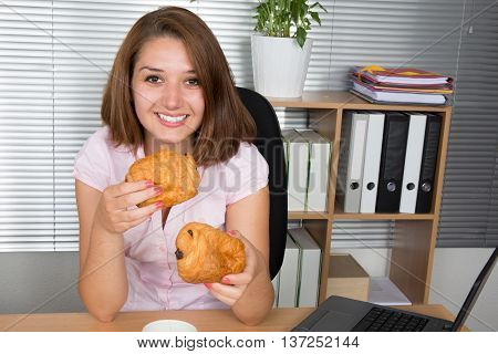Businesswoman Eating At Computer In Office At Work Place.