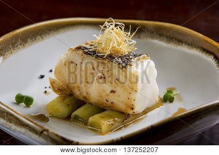 Fried toothfish with onion on dish in restaurant