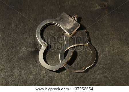 Security Steel Handcuffs On Black Wooden Background