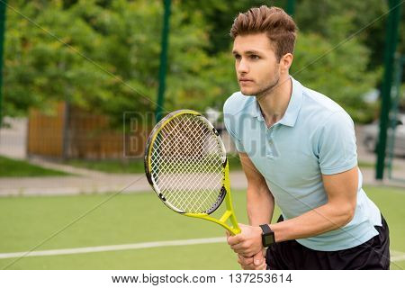 Confident male tennis player is waiting for ball. He is standing in position and looking forward with anticipation. Man is holding a racket