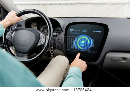 transport, green energy, technology and people concept - close up of man driving car and using eco system mode on board computer
