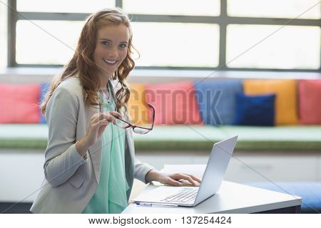 Portrait of smiling teacher using laptop in library