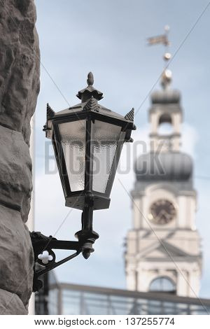Street lamp on the facade of an old house in the background the tower of City Hall in Riga with a clock and weather vane