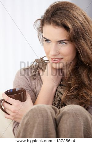 Young attractive woman sitting on sofa with legs pulled up, drinking tea, smiling.?