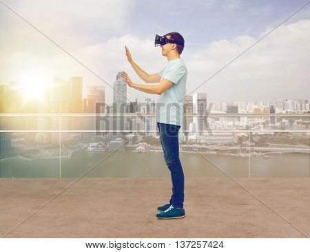 3d technology, virtual reality, entertainment, cyberspace and people concept - man with virtual reality headset or 3d glasses playing game and touching something over singapore skyscrapers background