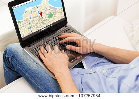 technology, location, navigation, people and lifestyle concept - close up of male hands typing on laptop computer with gps navigator map on screen at home