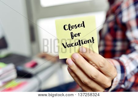 closeup of a young caucasian man showing a yellow note with the text closed for vacation, seating at his office desk