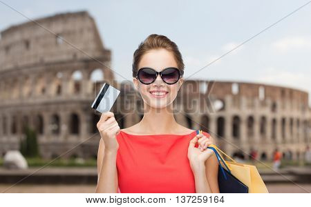 people, holidays, tourism, travel and sale concept - young happy woman with shopping bags and credit card over coliseum background