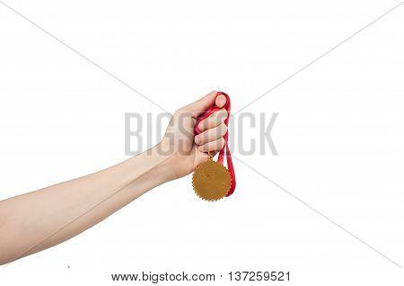 hand holding golden medal on white background.