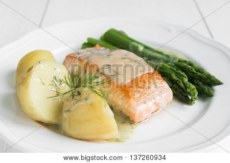 Close up of grilled salmon fillet with potatoes and asparagus garnished with dill sauce arranged on white plate