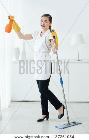 POrtrait of cheerful Asian chambermaid cleaning hotel room