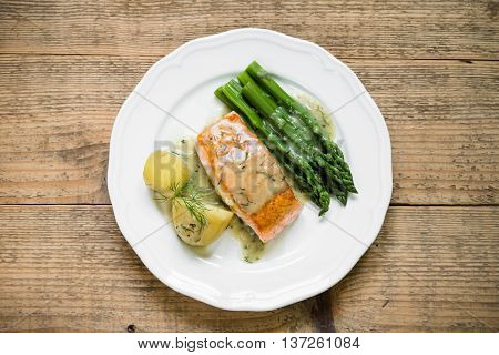 Top view of grilled salmon fillet with potatoes and asparagus garnished with dill sauce arranged on white plate and old wooden table