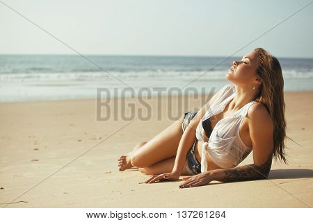 young pretty blond woman at seacoast walking relaxing, fashion lady at sunset, cool vacations