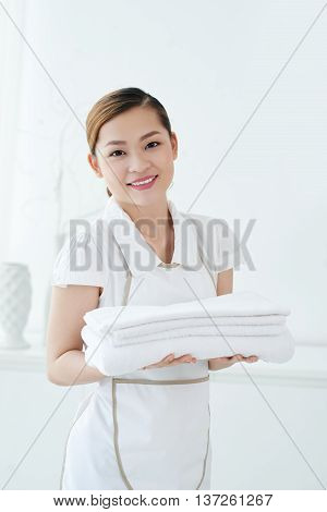 Pretty young chambermaid with stack of fresh towels