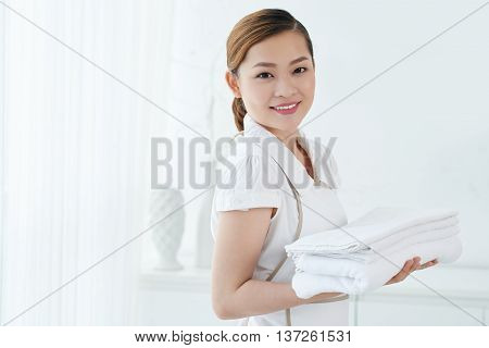 Lovely Vietnamese maid holding fresh white towels