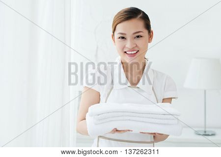 Beautiful smiling chambermaid changing towels in hotel room