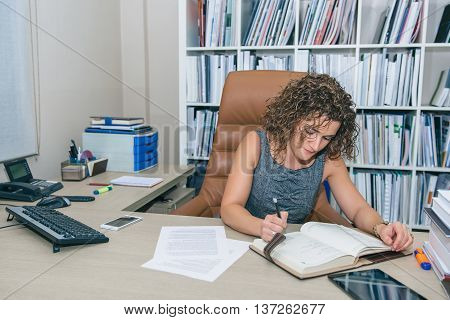 Portrait of businesswoman writing plans in notebook at workplace