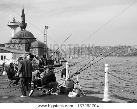 Istanbul Turkey - November 9 2014: Istanbul at the Bosphorus bonito bluefish mackerel sardines sea bass and other bottom fish hunt. Üsküdar Shamsi Pasha Mosque is seen in the background. Migration time increases in fishing catch fish. Üsküdar Shamsi Pasha