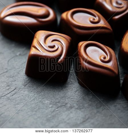 Delicious chocolate candies. Chocolates as background. Dark Chocolate Candy. Praline sweets. Low key photo