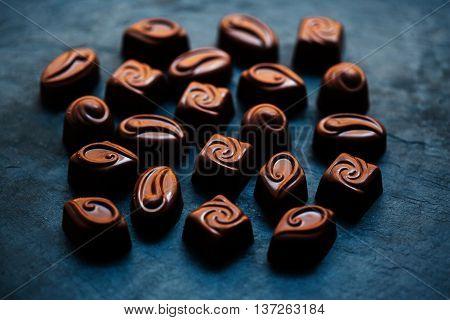 Chocolates background. Dark Chocolate Candy. Praline sweets. Low key photo