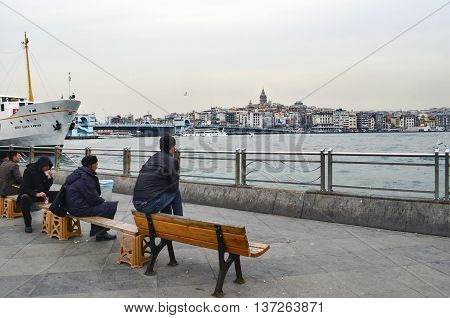 Istanbul Turkey - February 21 2013: Istanbul view. Eminönü pier Galata bridge and Galata tower. People are resting on the bench.