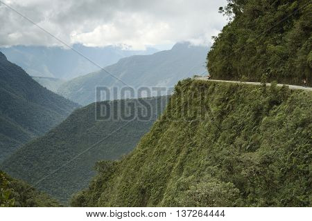 Cyclists riding on the Death Road - the most dangerous road in the world, North Yungas, Bolivia.