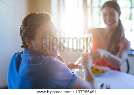 Portrait of young couple toasting champagne flutes while having lunch in a restaurant