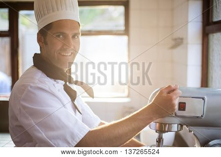 Portrait of chef in commercial kitchen blending the batter in mixing blender