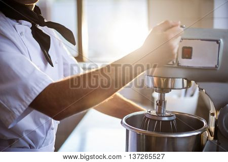 Mid section of chef in commercial kitchen blending the batter in mixing blender