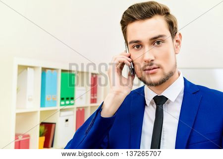 Handsome businessman talking on his cell phone at the office.