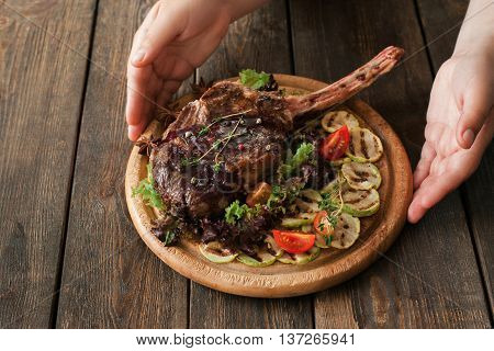 Portion of roasted rib steak on board serving. Hands put on wooden table dish with grilled pork on bone