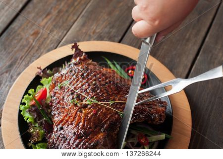 Cutting grilled duck thigh close-up top view. Hands carving of roasted poultry leg with two-pronged fork and knife on wooden background
