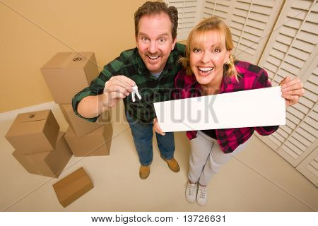 Goofy Couple Holding Keys and Blank Sign in Room with Packed Cardboard Boxes.