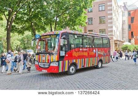 RIGA LATVIA - JULY 05 2016: Red city sightseeing bus waiting for tourists near Church of St Peter in Riga Latvia. Povides excursion tours around old Riga (UNESCO site)
