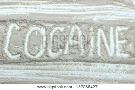 drugs concept Word Cocaine written over white powder