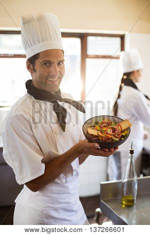 Portrait of happy head chef presenting his salad in commercial kitchen