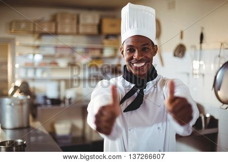 Portrait of chef standing in kitchen showing thumbs up