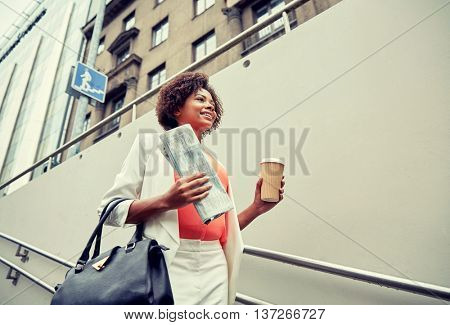 business and people concept - young smiling african american businesswoman with coffee cup going down stairs into city underpass