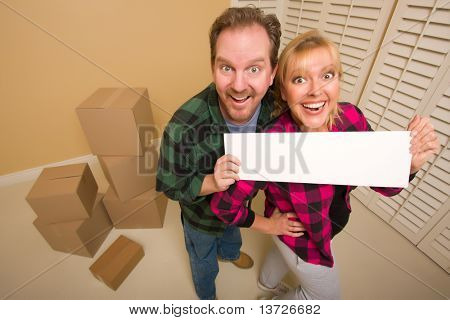 Happy Goofy Couple Holding Blank Sign in Room with Packed Boxes.