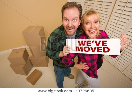 Goofy Couple Holding We've Moved Sign in Room with Packed Cardboard Boxes.