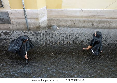 ROME ITALY - JUNE 20 2016: People under rain in Lungaretta street the Trastevere pedestrian area