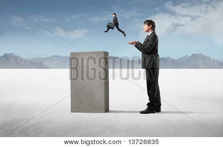 Businessman helping a smaller one to jump on a high cube