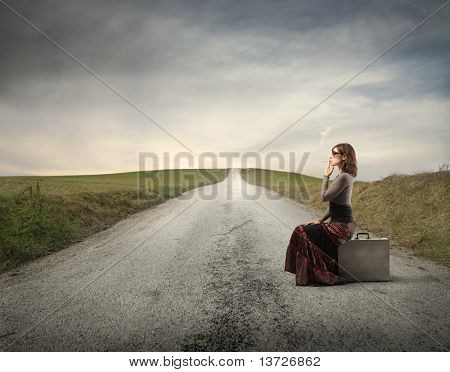 Woman sitting on a suitcase on a countryside road and smoking a cigarette