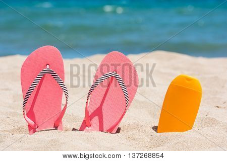 Sunscreen bottle and pink flip flops on the beach